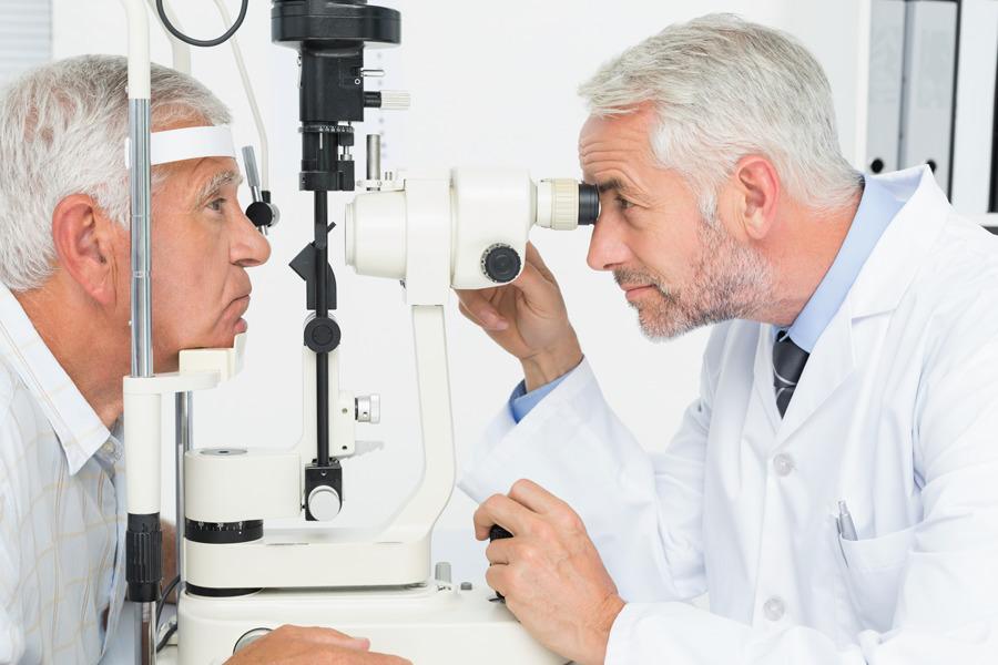 Médico oftalmologista examina paciente idoso com catarata
