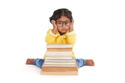 Menina tristonha usando óculos infantis de armação de acetato sentada no chão apoiando os cotovelos sob uma pilha de livros