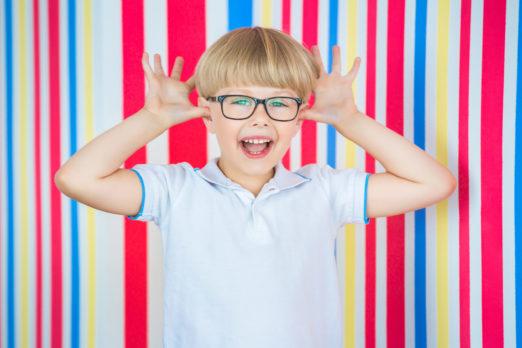 Garoto sorridente comas mãos nas orelhas usando óculos infantis na frente de uma parede com listrar azul, amarela e vermelha