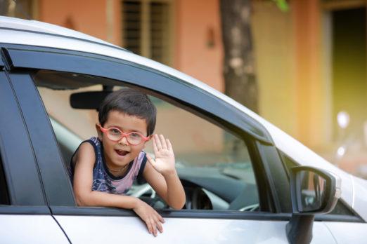 Menino sorridente usando óculos infantis com lente de policarbonato se projetando para fora da janela de uma carro
